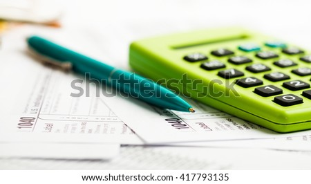 Business work station with paperwork income tax return, calculator and pen and dollar - stock photo