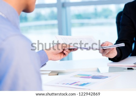 Business worker passing a pile of documents to his colleague - stock photo