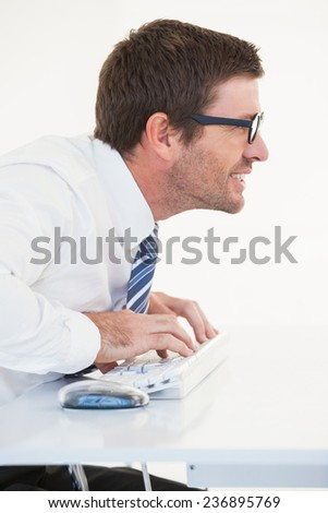 Business worker with reading glasses on computer on white background - stock photo