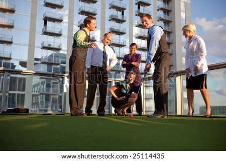 Business workers playing golf outside office, having fun