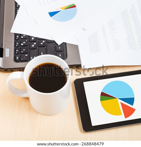 business workflow - above view mug of coffee and tablet pc with chart on office table - stock photo