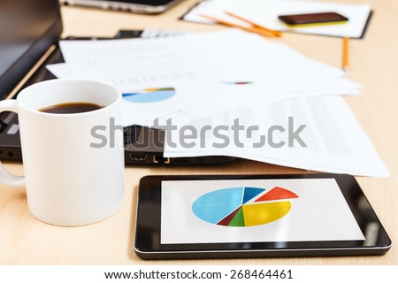 business workflow - mug of coffee and tablet pc with chart on office table - stock photo