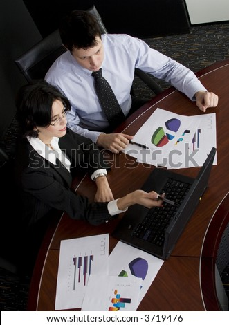 Business workgroup interacting in a boardroom setting using laptop - stock photo