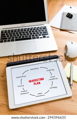 Business working desk with tablet showing marketing planning - stock photo