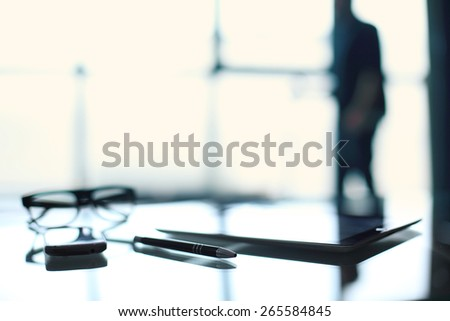 Business workplace. Blurred figure of a man in an office building, a desk workstation - stock photo