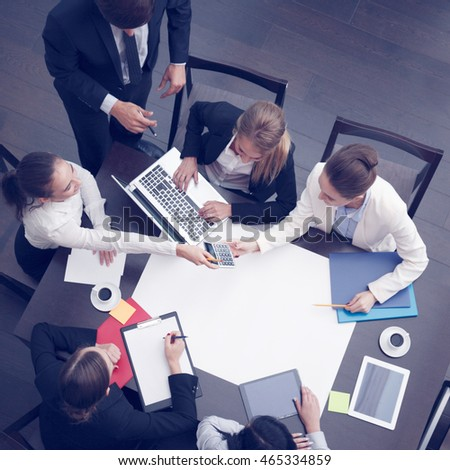 Business workplace with people, cup of coffee, digital tablet, smartphone, papers and various office objects on table