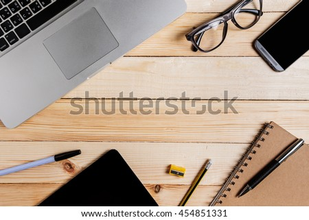 Business workspace with notepad laptop pencil glasses sharpener tablet and smartphone on wood table. - stock photo