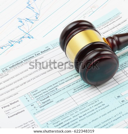 Business world and its symbols - wooden judge's gavel over USA 1040 Tax Form