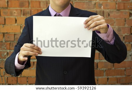 Business young man holding a blank white sheet of paper. - stock photo