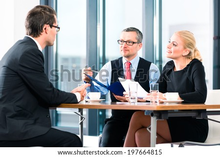 Business - young man in an Job interview, hands over his application papers to the boss and his female assistant in their office - stock photo