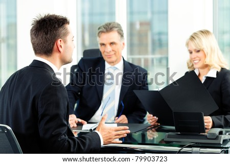 Business - young man sitting in job Interview - stock photo