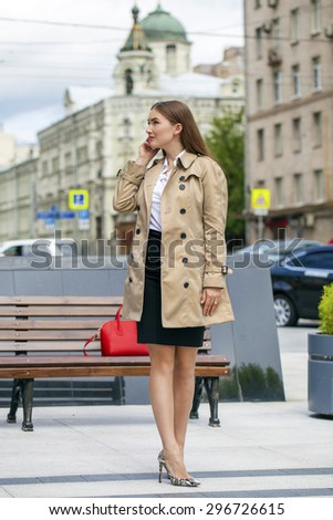 Business young woman in a beige raincoat talking on his cell phone on the street - stock photo