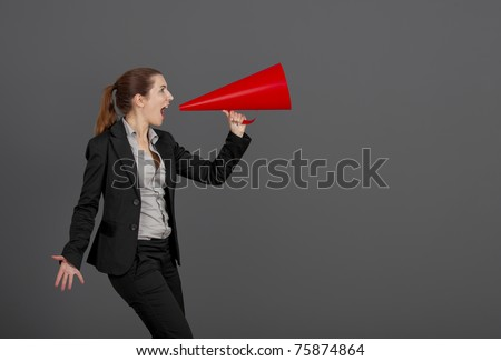 Business young woman speaking to a megaphone, over a grey background - stock photo