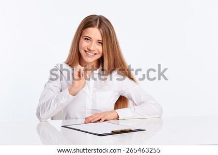 Business young woman writes on the folder at the table