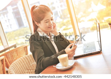Business young women use phone in cafe. Image is Instagram filtered  - stock photo