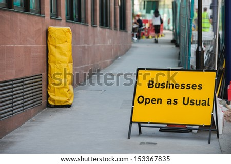 Businesses open as usual sign during re construction of a busy public street in a capital city. - stock photo