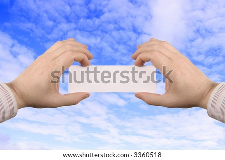 businesskort in the hands, towards the blue sky - stock photo