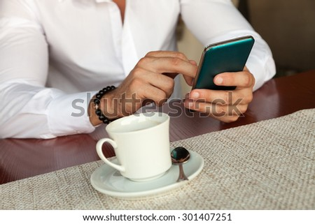 Businessma in restourant with smartphone - stock photo