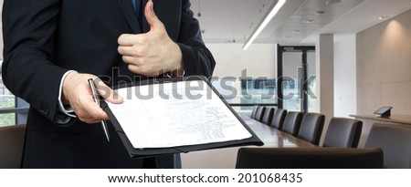 Businessman about handing an agreement contract on office background - stock photo