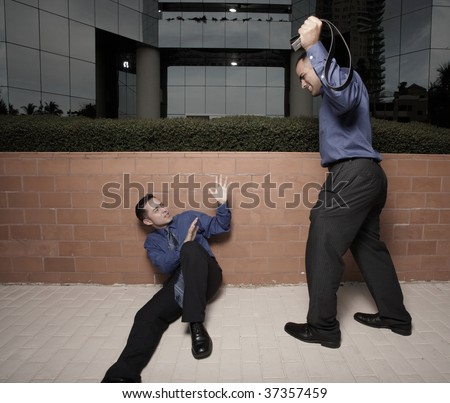 Businessman about to beat another businessman with a belt