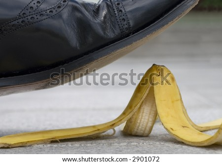 Businessman about to have an accident by slipping on a banana skin or peel. - stock photo