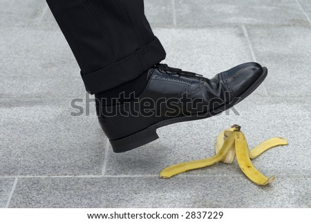 Businessman about to have an accident by stepping on a banana skin. - stock photo