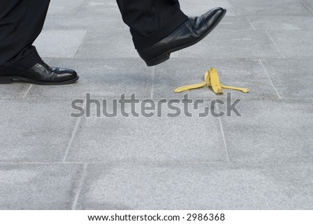Businessman about to have an accident by stepping on a banana skin or peel.  Space for copy. - stock photo