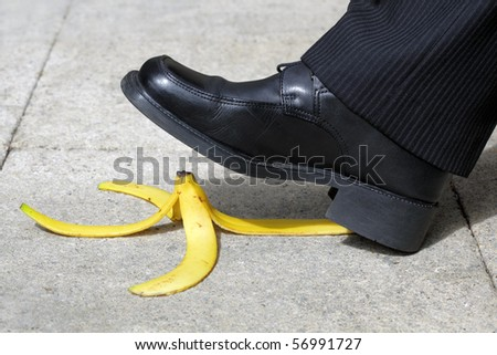 Businessman about to slip and fall on a banana skin - stock photo