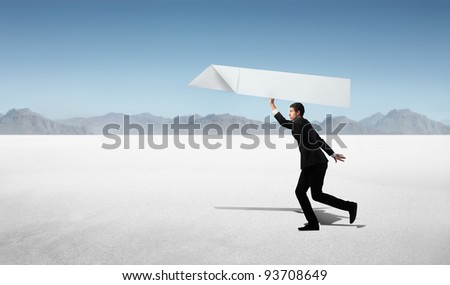Businessman about to throw a plane model in a desert - stock photo