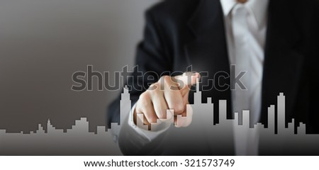 Businessman Activate Growth Process, choosing house, real estate city concept. Skyline Hand pressing the house icon on virtual screen. Business, technology, internet and networking concept. Copy space - stock photo