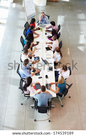 Businessman Addressing Meeting Around Boardroom Table - stock photo