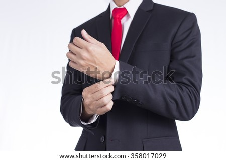 Businessman Adjusting Cufflinks his Suit - stock photo