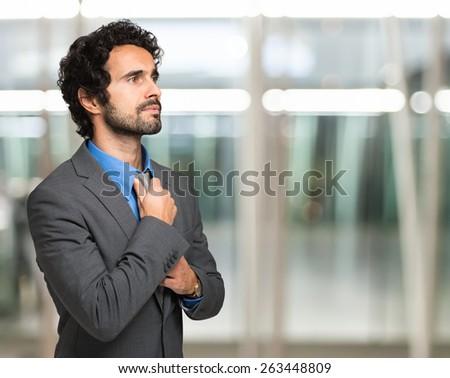 Businessman adjusting his necktie. Copy-space - stock photo