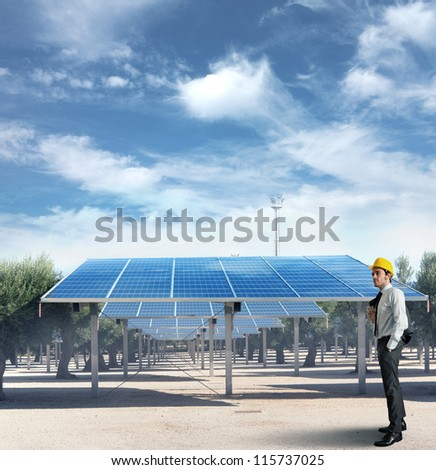 Businessman against an installation of solar panel - stock photo
