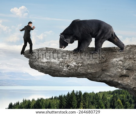 Businessman against black bear balancing on cliff with sky trees landscape background - stock photo