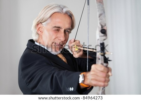 Businessman aiming at target with bow and arrow