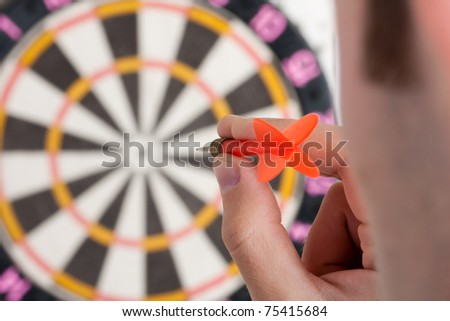 Businessman aiming to target by red dart - stock photo