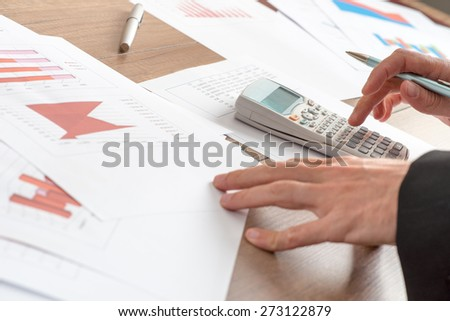 Businessman analysing statistical graphs using a manual calculator at his desk in the office, close up view of his hands and paperwork.