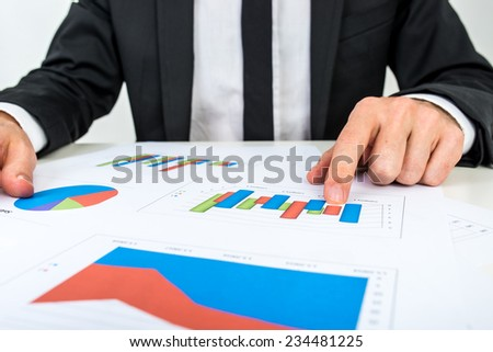 Businessman analyzing a set of bar graphs as he sits at his desk pointing to one column chart, in a business analysis, projections and strategy concept. - stock photo