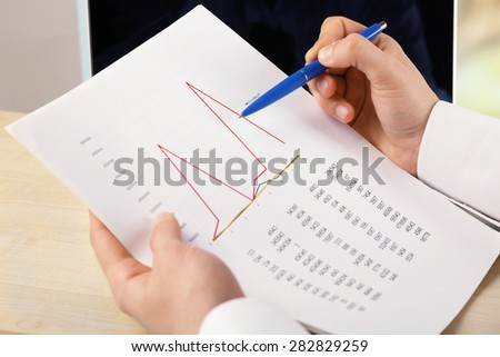 Businessman analyzing charts, closeup