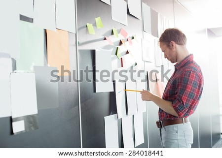 Businessman analyzing documents on wall at creative office - stock photo