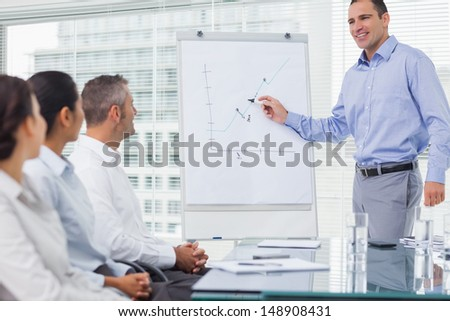 Businessman analyzing graph during presentation in bright office - stock photo