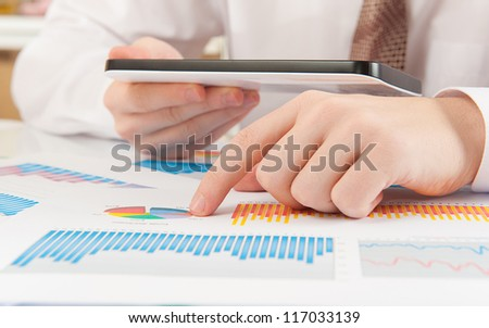 Businessman analyzing graphs using modern digital tablet device - stock photo