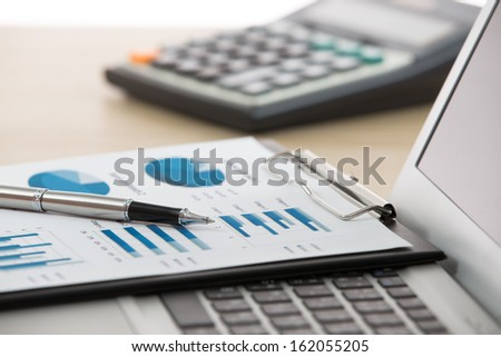 Businessman analyzing investment charts with laptop