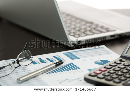 Businessman analyzing investment charts with laptop - stock photo