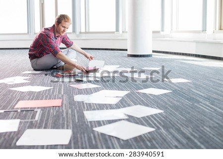 Businessman analyzing photographs while sitting on floor at creative office - stock photo
