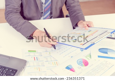 Businessman analyzing report on chart with laptop