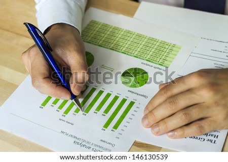 Businessman analyzing sustainable development opportunities charts at workplace. Hand holding a pen and green charts. - stock photo