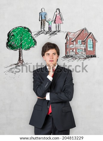 Businessman and a concept of a dream life: a family, a tree and a house.  - stock photo