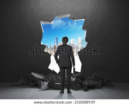 Businessman and a Hole in a concrete wall with city view  - stock photo